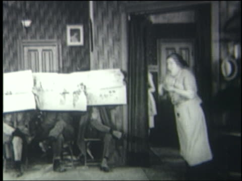b/w 1923 woman blows whistle, men reading newspapers stand up + run out of room - 1923 stock videos & royalty-free footage