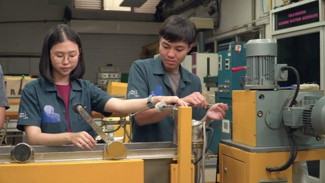 vídeos y material grabado en eventos de stock de mujer trabajadora de cuello azul ayudar a un ingeniero asiático amigo haciendo línea de producción de polímeros de investigación para producir extrusión de polímero. estudiante científico con amigo vestido de ropa azul haciendo experimentos poniend - trabajador de línea de montaje