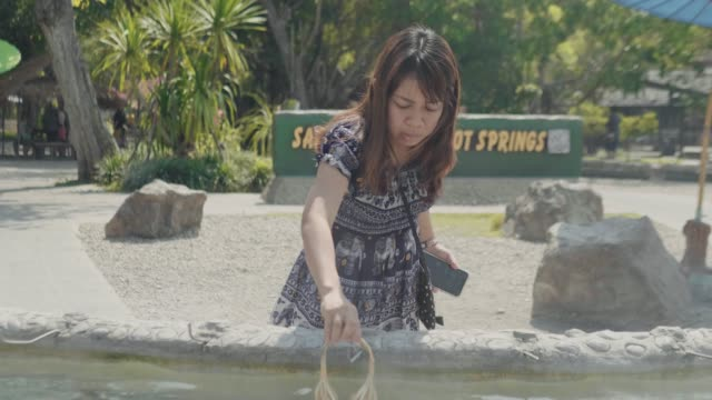 woman boiling eggs in thermal pool - thermal pool stock videos & royalty-free footage