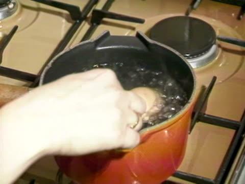 vídeos y material grabado en eventos de stock de woman boils hard boiled eggs in a kitchen. 1988. - hervido