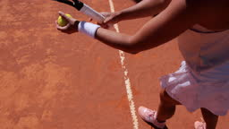 Woman bouncing ball before serving on tennis court
