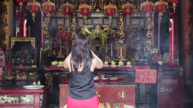 stockvideo's en b-roll-footage met a woman bows and prays at a temple in chinatown, singapore. - gelovige