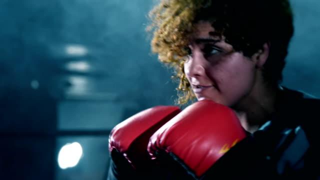 vídeos y material grabado en eventos de stock de mujer boxer training con su coach - cámara de aislamiento con guantes