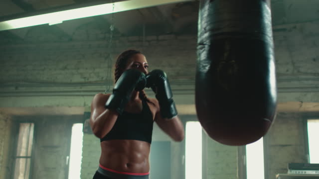 woman boxing punshing bag - strength stock videos & royalty-free footage