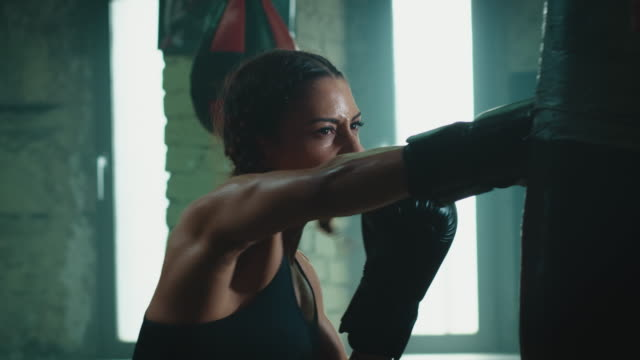 woman boxing punshing bag - boxing stock videos & royalty-free footage