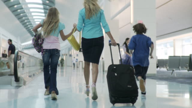 MS POV Woman, boy and girl running through concourse in airport / Jacksonville, FL, United States