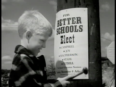 Woman boy putting up posters on telephone poll CU Boy hammering 'Better Schools' LA MS Woman reading pamphlets WS Girl putting pamphlet on doorstep...