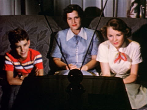 1950 woman, boy + teen girl sitting on sofa watching television / industrial / jump cut