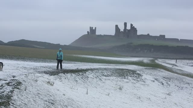 A woman bracing the storm surrounded by foam wipped up by storm waves blowing ashore at Craster on the Northumberland coast with Dunstanburgh Castle in the background.
