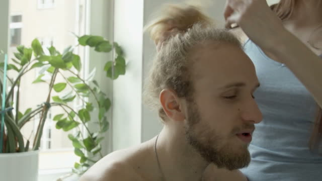 woman braiding boyfriend's hair - day in the life stock videos & royalty-free footage