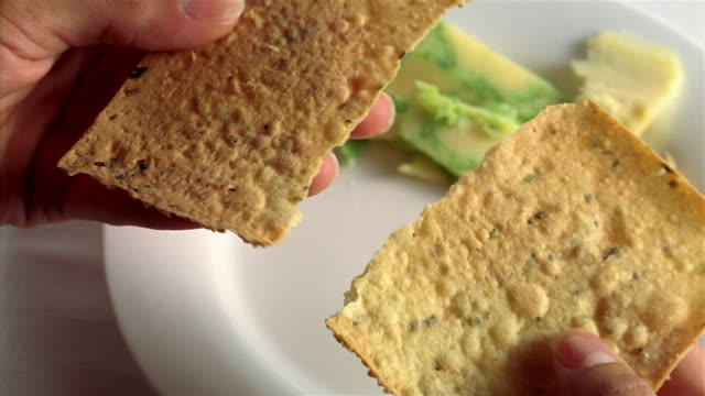 ecu shaky woman braking bread, placing on plate - cracker stock videos and b-roll footage