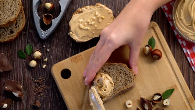 4k woman bread slice peanut butter riding - butter stock videos & royalty-free footage