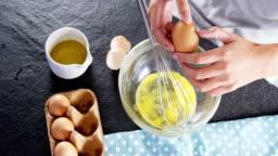 Woman breaking eggs into a bowl 4k