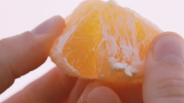 vidéos et rushes de woman breaking piece of orange apart - acide ascorbique