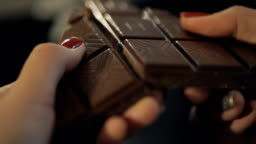 Woman breaks chocolate bar. Slow motion