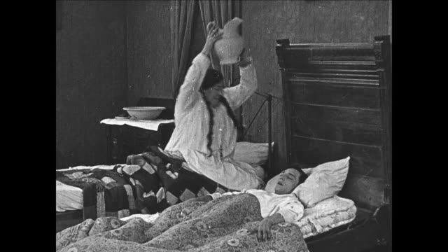 1922 Woman breaks water pitcher on surprised man's (Buster Keaton) head after he struck her when he was pretending to be asleep