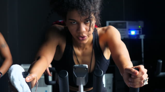 vidéos et rushes de cu woman breathing heavily while riding indoor bike in cycling studio - exercice physique