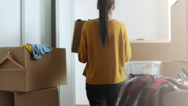 woman bringing in cardboard box with things in her new apartment - unpacking stock videos & royalty-free footage