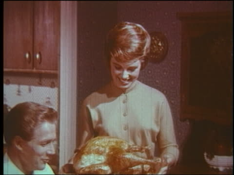 1960 woman bringing turkey to dinner table