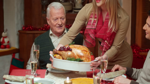 Woman bringing turkey to the Christmas table and  family applauds