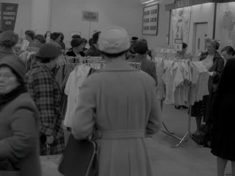 vidéos et rushes de a woman browses a rails of blouses in a department store 1957 - store
