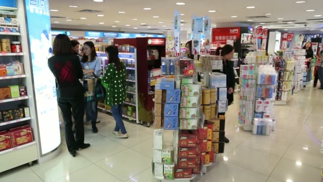 A woman browses cosmetic products in a Watsons store operated by A S Watson Co in the Tsim Sha Tsui district of Hong Kong A woman browses medicine in...
