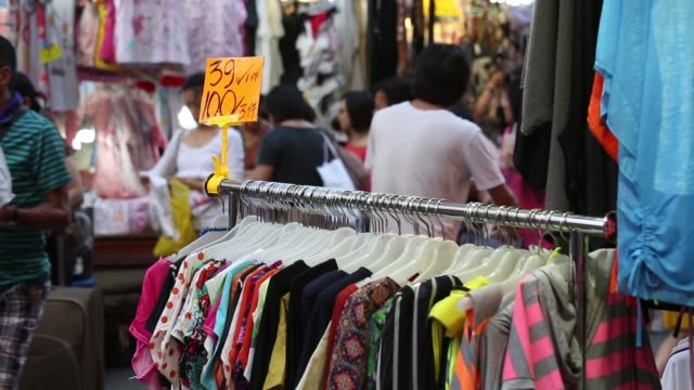 a woman browses for clothes in a market in the mong kok district of hong kong shoppers walk through a street market a price tag sits on a clothes... - mong kok stock videos and b-roll footage