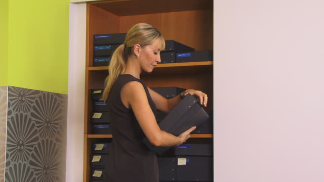 ms, woman browsing boxes in office wardrobe, berlin, germany - searching video stock e b–roll