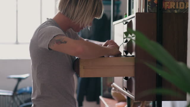 woman browsing drawers - cercare video stock e b–roll