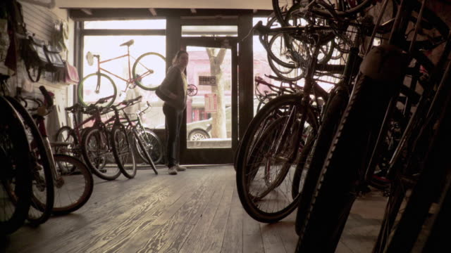 vidéos et rushes de ms la tu td woman browsing in bicycle shop, shop assistant approaching her, brooklyn, new york city, new york state, usa - entrée