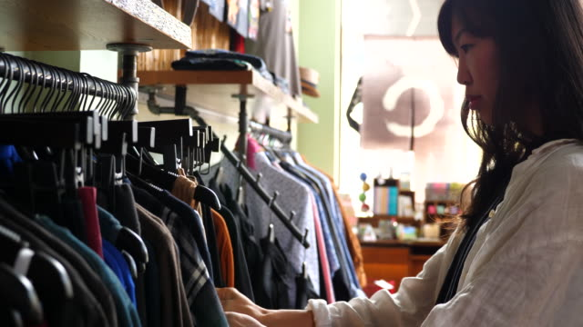 ms woman browsing through clothing rack and looking at pants while shopping in boutique - clothes rail stock videos & royalty-free footage