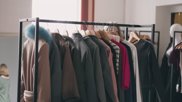 woman browsing through coats on rack - decisions stock videos & royalty-free footage