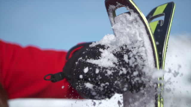 a woman brushes snow off her skis with glove to go skiing in the snow at a ski resort. - slow motion - sci attrezzatura sportiva video stock e b–roll