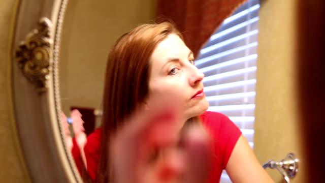 Woman Brushing Her Hair In Mirror