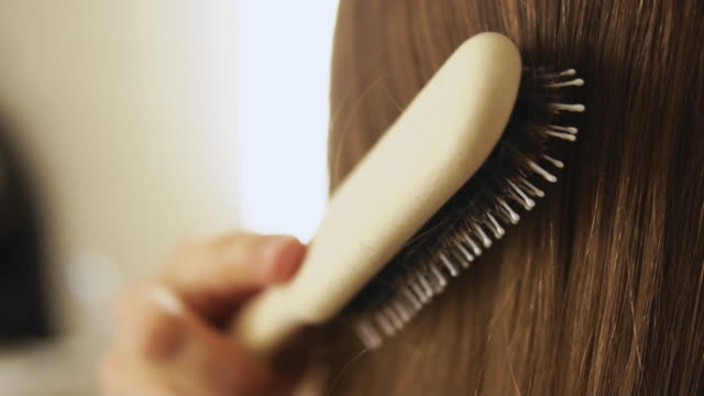 vídeos y material grabado en eventos de stock de woman brushing long blond hair. - cepillar el cabello