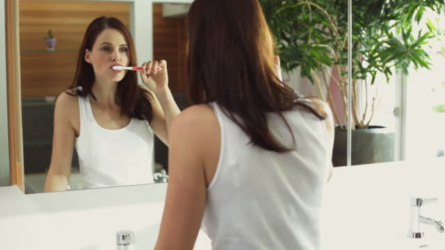 ms woman brushing teeth in front of mirror / kleinmachnow, brandenburg, germany - toothbrush stock videos & royalty-free footage