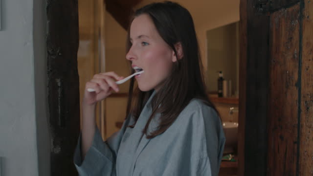 woman brushing teeth in hotel - brushing teeth stock videos & royalty-free footage