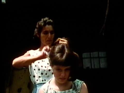 1969 montage ms woman brushing young girl's hair on front porch/ ms young girl standing at porch/ ms shirtless young boy sitting in porch/ ms man with arms crossed sitting idly on porch/ usa/ audio - appalachen region stock-videos und b-roll-filmmaterial