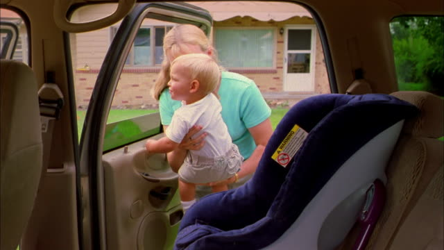 a woman buckles a toddler in a car seat. - safety stock-videos und b-roll-filmmaterial