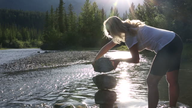 woman builds zen rock stack in mountain creek, sunrise - stack rock stock videos and b-roll footage