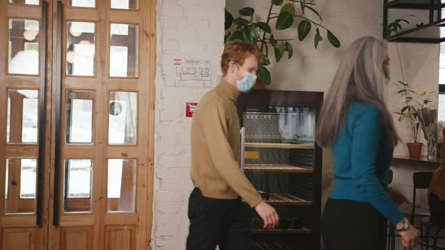 woman bumps elbow waves hand to greet man in mask in cafe - greeting stock videos & royalty-free footage
