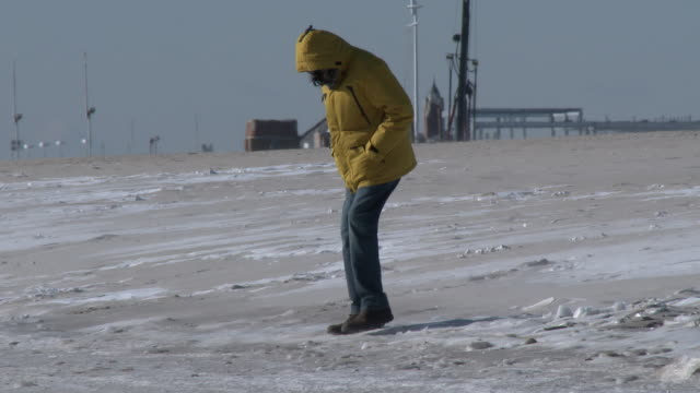 A woman bundled up from head to toe breaks up thick ice on the sand at Jones Beach New York caused when ocean water and sea spray froze due to bitter...
