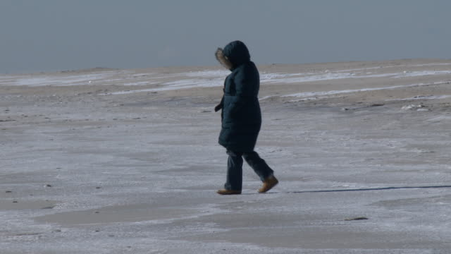A woman bundled up from head to toe from the bitter cold temperatures walks over frozen sea spray covering the sand on Jones Beach New York during an...