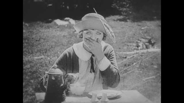 1923 woman (phyllis haver) burns tongue sipping too hot coffee - 無声映画点の映像素材/bロール