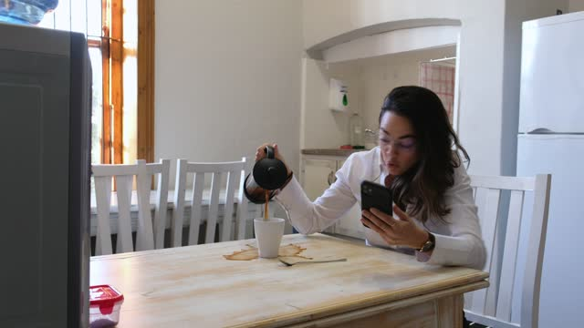 woman busy on her phone spills coffee all over the table - blooper film clip stock videos & royalty-free footage