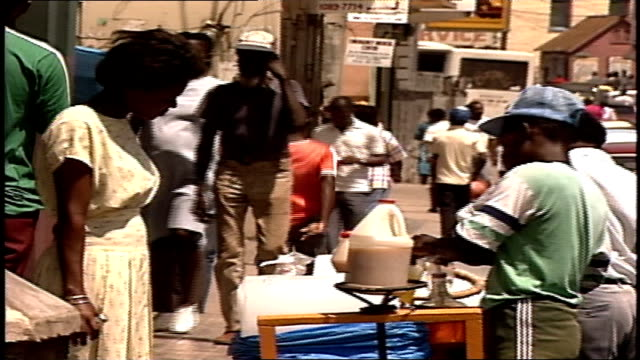 Woman Buying a Drink From Kids with Drink Cart in Street in Jamaica