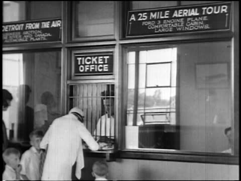 b/w 1927 woman buying airplane tickets from man at booth of early airline / newsreel - ticket counter stock videos & royalty-free footage