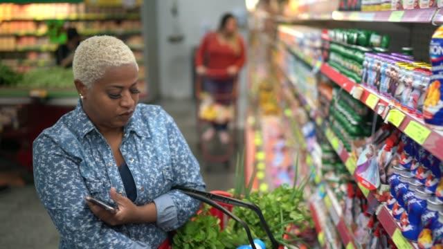 stockvideo's en b-roll-footage met vrouw die bij supermarkt koopt gebruikend mobiele telefoon - dairy product