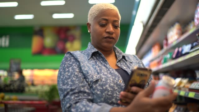 woman buying at supermarket using mobile phone - list stock videos & royalty-free footage