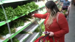 Woman buying at supermarket using mobile phone